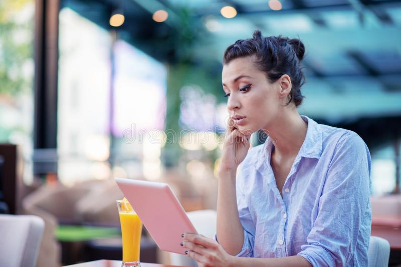 Jong en mooi meisje met notitieboekje en laptop zitting in een koffie stock foto's