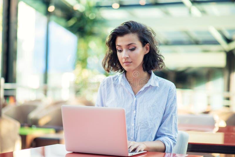 Jong en mooi meisje met notitieboekje en laptop zitting in een koffie royalty-vrije stock foto's