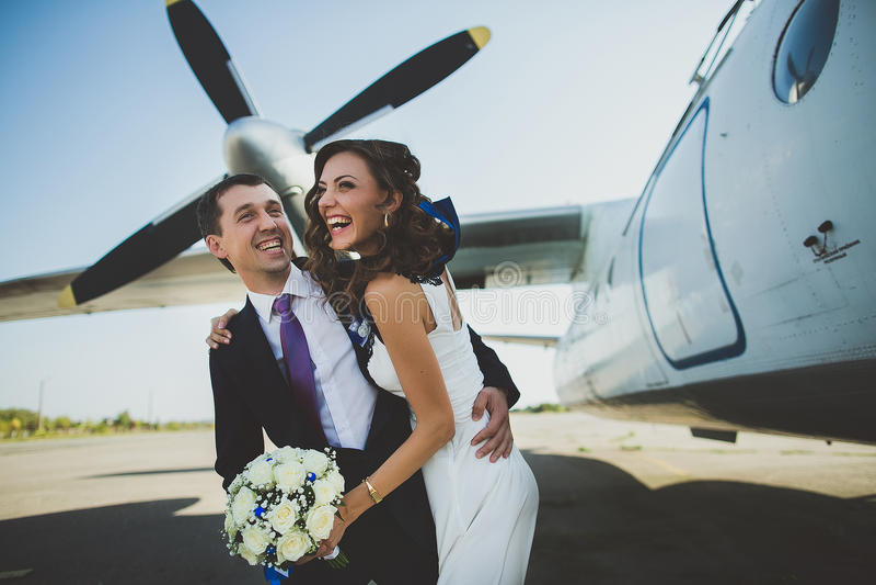 Jong en mooi paar in sweateshoeden die pret hebben die samen dichtbij het vliegtuig op het vliegveld koesteren royalty-vrije stock fotografie