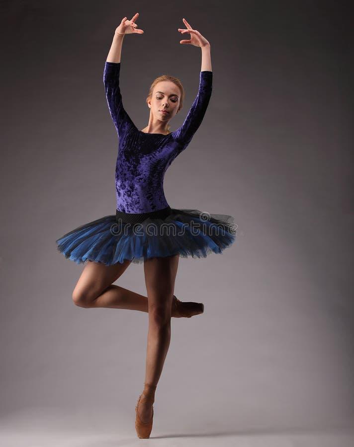 Jong en ongelooflijk stelt de mooie ballerina in blauwe uitrusting en danst in studio Klassiek balletart. Op één been stock foto
