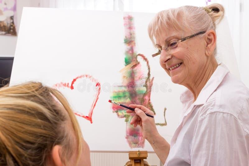 Jong en oud samen terwijl het schilderen royalty-vrije stock afbeelding