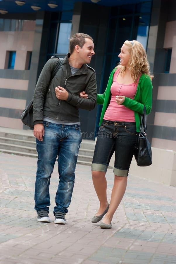 Jong en paar dat loopt spreekt stock afbeelding