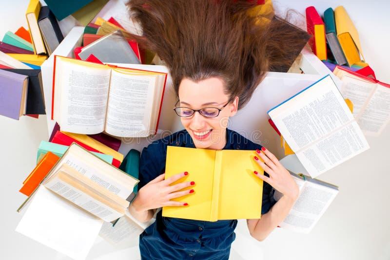 Jong en slim meisje die die met boek liggen door kleurrijk boek wordt omringd stock fotografie