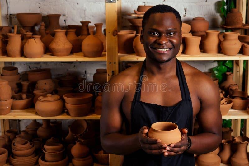 Jong en zelfverzekerd voor de amerikaanse man in een zwart platform sculpt een potter uit een klei-aardewerkplaats kleipot in stock fotografie