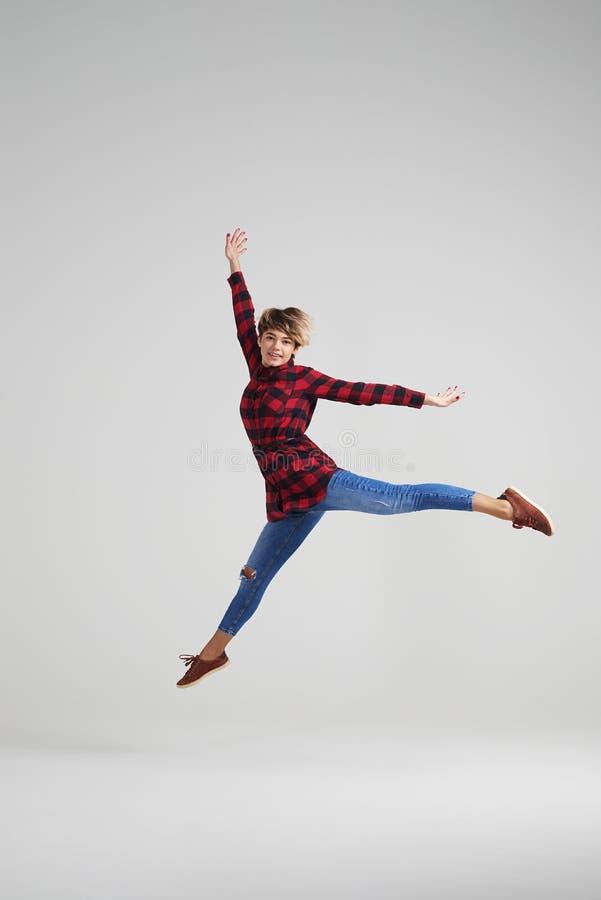 Jong energiek meisje die bij studio springen royalty-vrije stock afbeelding