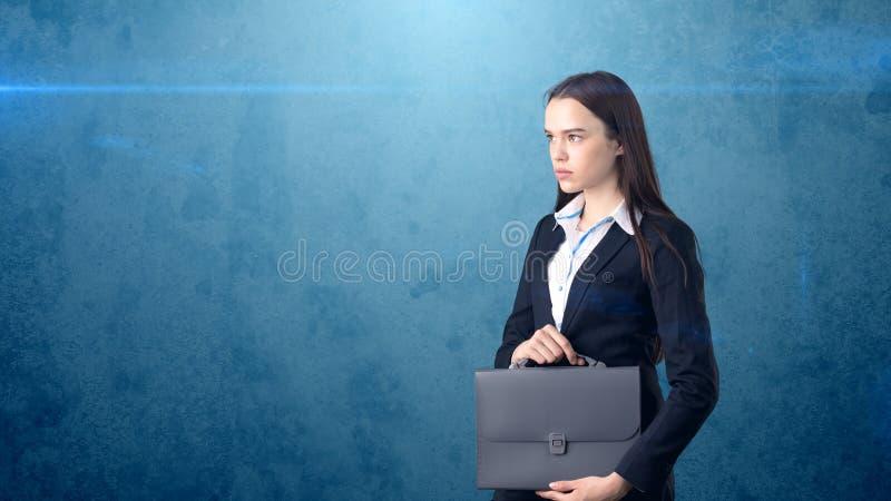 Jong ernstig mooi onderneemsterportret met grijze aktentas, donkere achtergrond royalty-vrije stock fotografie