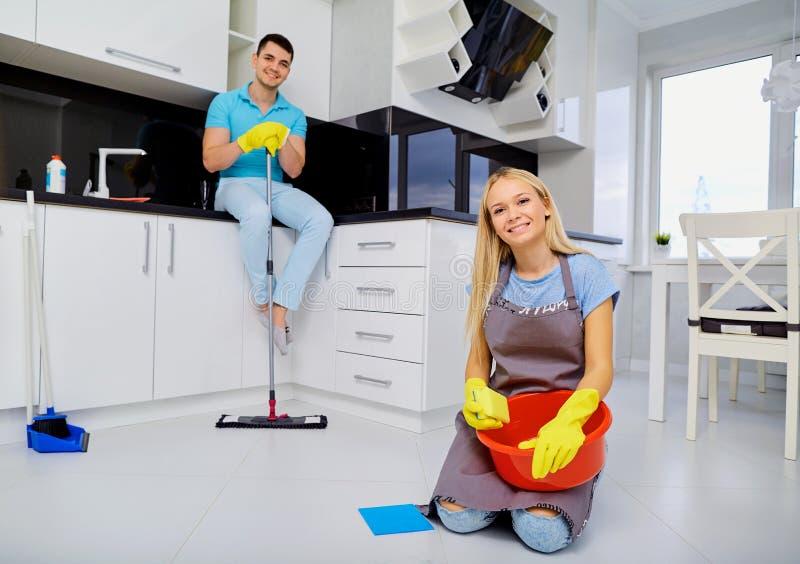 Jong familiepaar die het schoonmaken in de keuken doen stock afbeelding