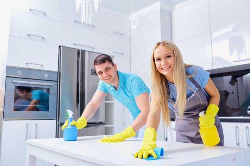 Jong familiepaar die het schoonmaken in het huis doen stock foto