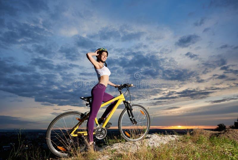 Jong fietserwijfje op fiets bovenop berg met mooi landschap bij zonsondergang royalty-vrije stock afbeeldingen