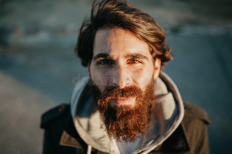 Jong gebaard kerelportret, met de zon in het gezicht, met stedelijke stijlkleren  stock foto's