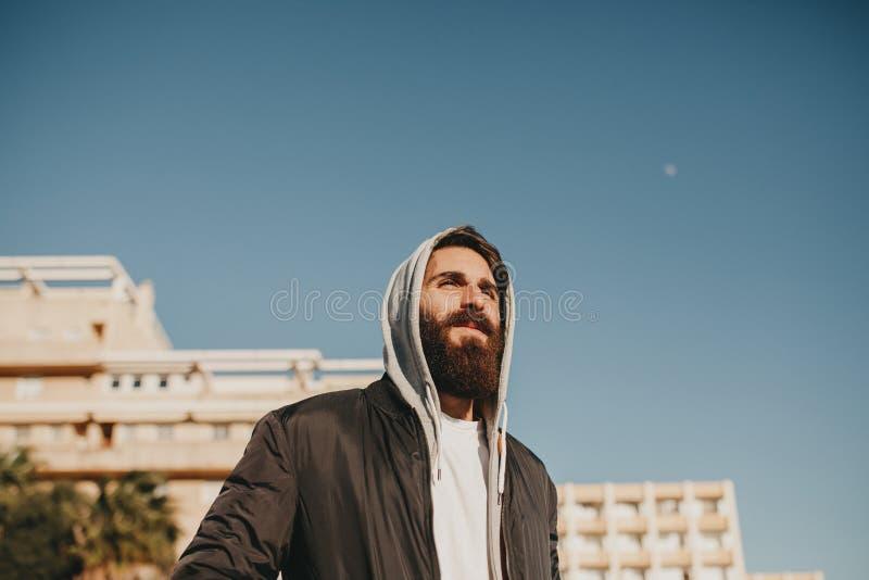 Jong gebaard mensenportret, met de zon in het gezicht, met de stedelijke kleren van de straatstijl royalty-vrije stock fotografie