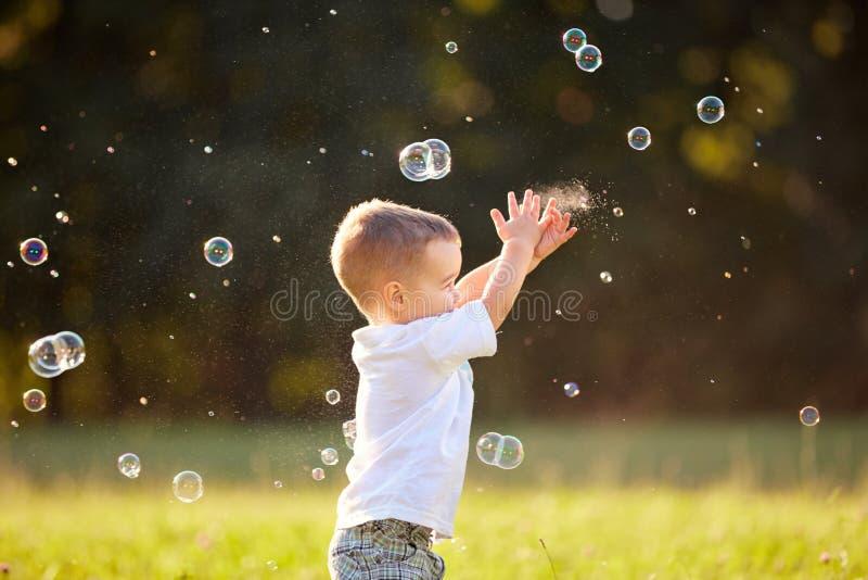 Jong geitje in aard die zeepbels bereiken stock afbeeldingen