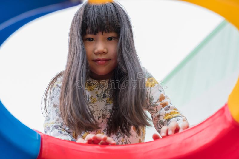 Jong geitje Aziatisch meisje die pret hebben op kinderen te spelen ` die s stuk speelgoed beklimmen bij royalty-vrije stock foto