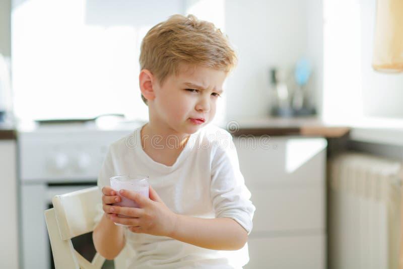 Jong geitje of blonde gelukkige jongen die bij lijst eten Kinderjaren en geluk, onafhankelijkheid Ontbijt, ochtend, familie Klein stock foto's