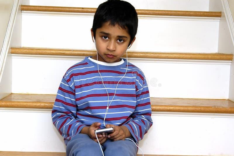 Jong geitje dat aan muziek luistert royalty-vrije stock afbeeldingen