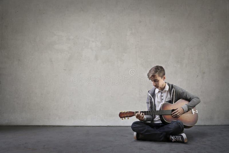 Jong geitje dat de gitaar speelt stock foto