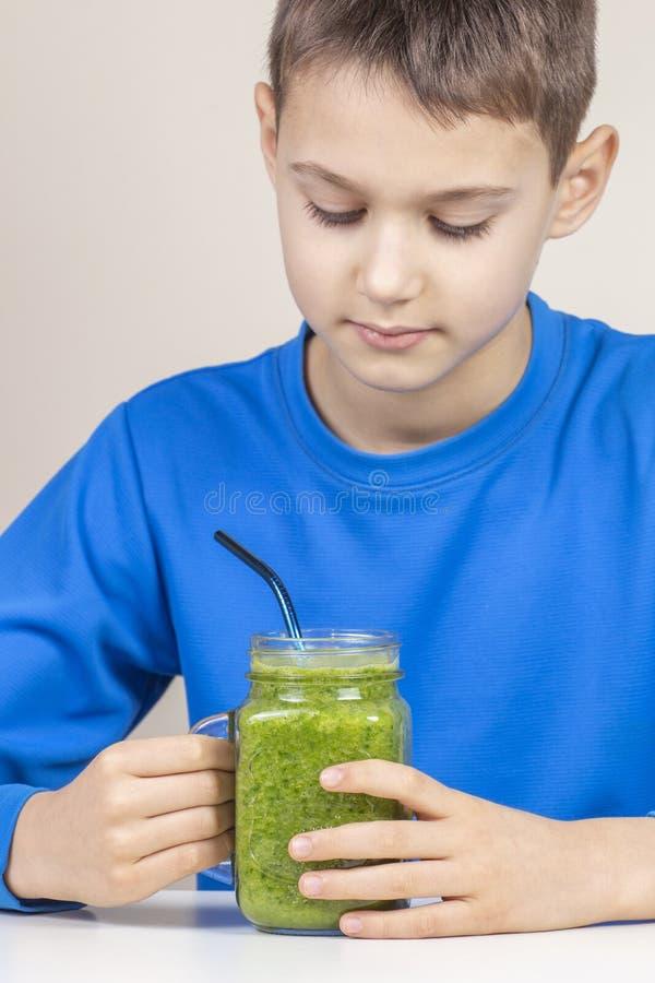 Jong geitje die gezonde groene smoothiecocktail thuis drinken stock foto's