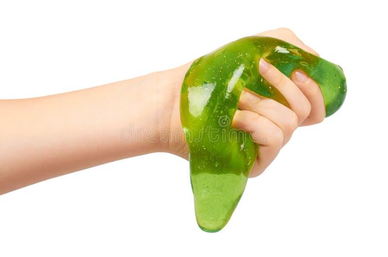 jong geitje die groen slijm met hand, transparant stuk speelgoed spelen stock foto