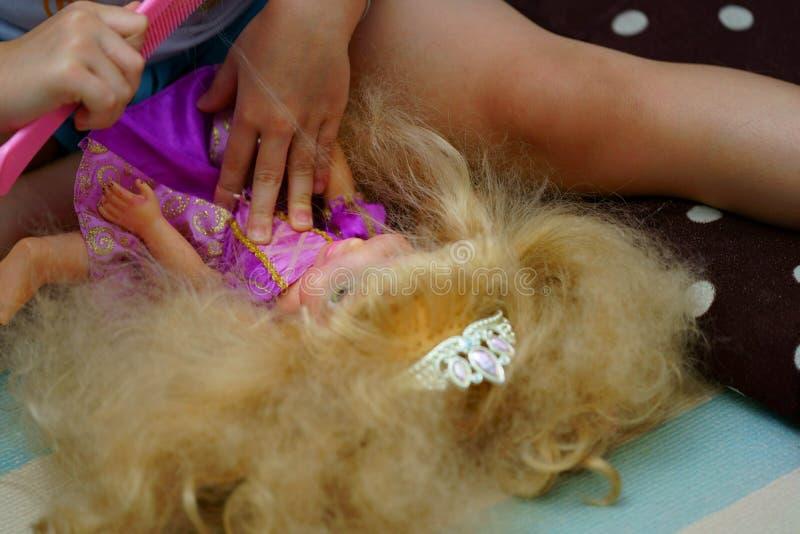 Jong geitje die haar van prinsespop kammen royalty-vrije stock afbeelding
