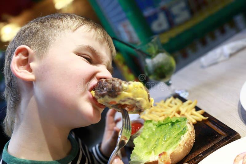 Jong geitje die hamburger eten stock foto's