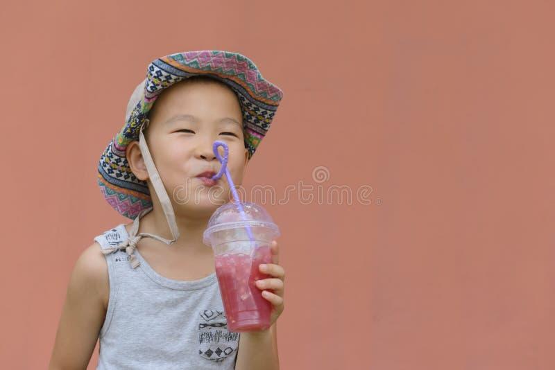 Jong geitje die koude drank drinken stock foto