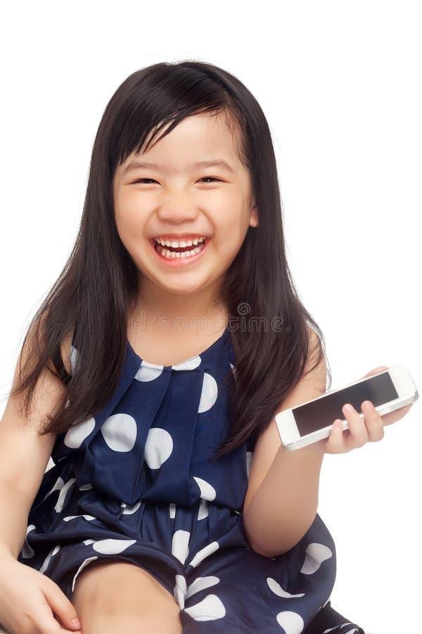 Jong geitje die met in hand smartphone lachen stock foto