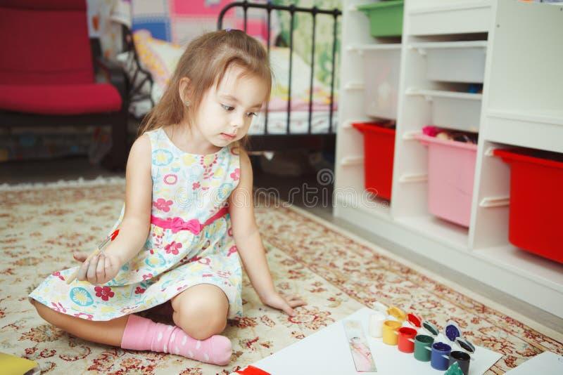 Jong geitje die neer op blad van document kijken die op vloer wordt geplaatst stock afbeeldingen