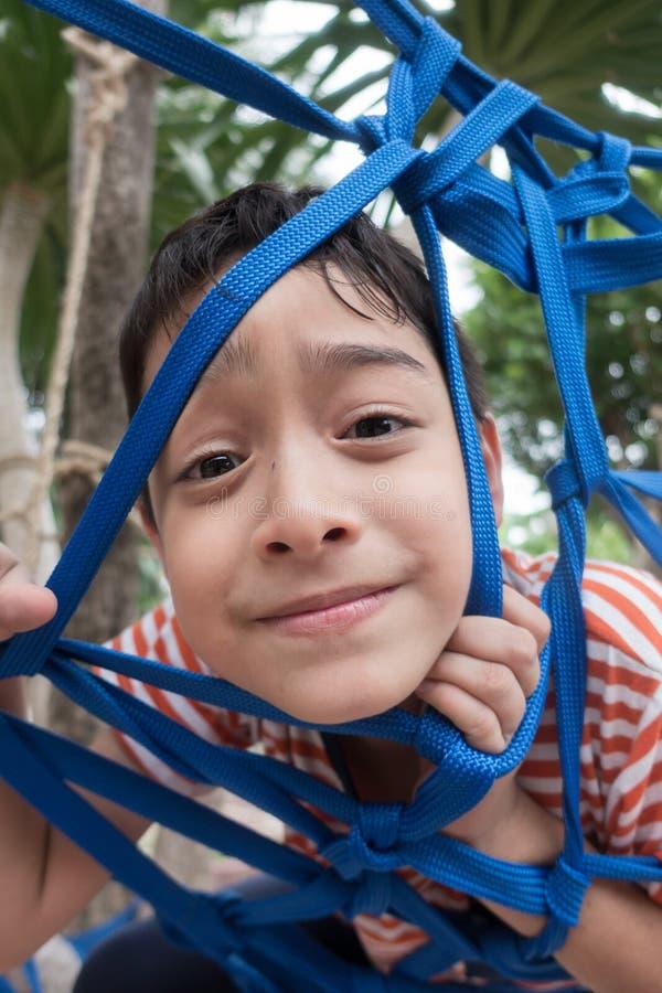 Jong geitje die op de boom met kabel netto openluchtactiviteit beklimmen stock afbeelding