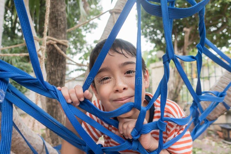 Jong geitje die op de boom met kabel netto openluchtactiviteit beklimmen stock foto