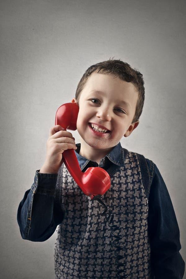 Jong geitje die op de telefoon spreken stock fotografie