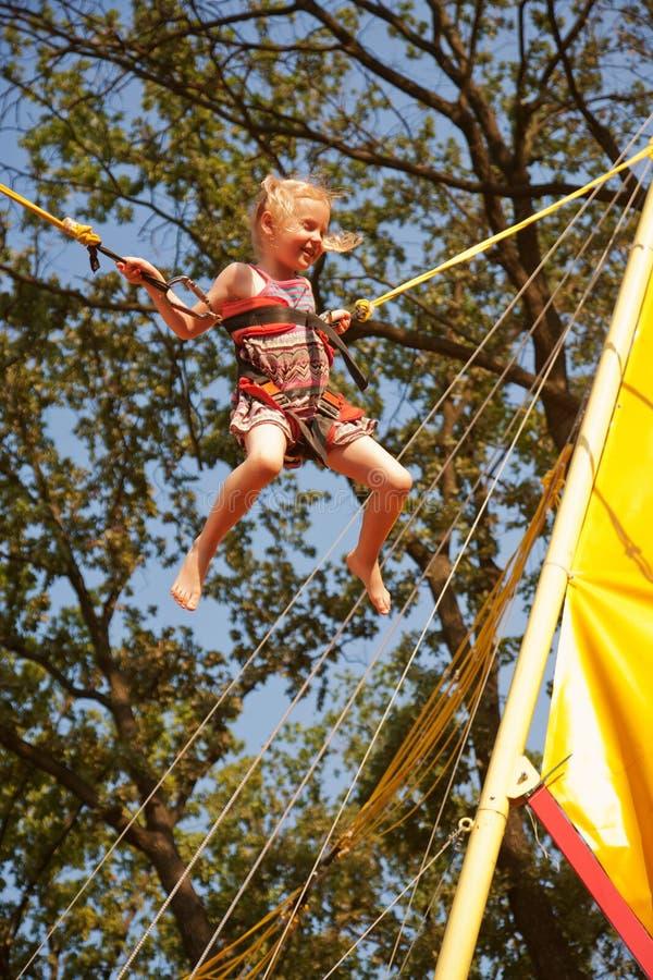 Jong geitje die op de trampoline springen stock afbeelding