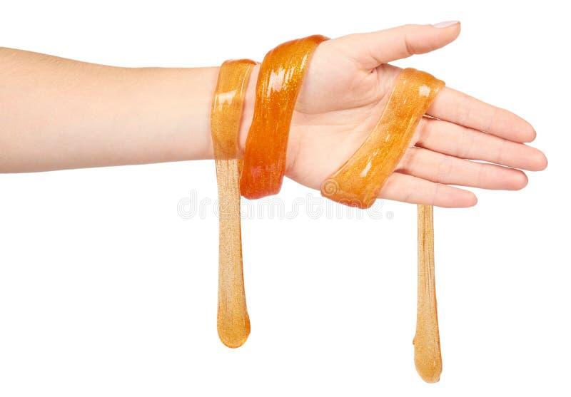 jong geitje die oranje slijm met hand, transparant stuk speelgoed spelen royalty-vrije stock afbeeldingen