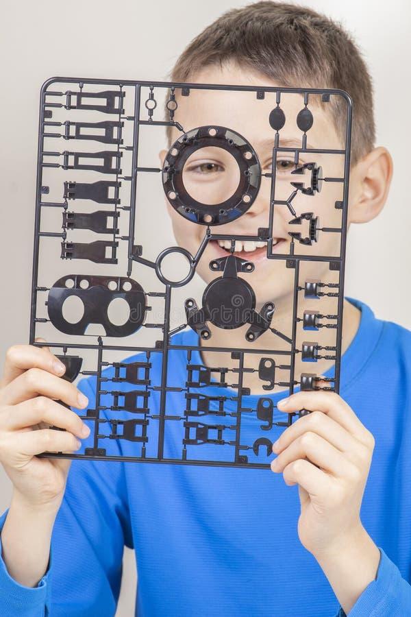 Jong geitje die pret hebben terwijl thuis het maken van robot Glimlachende jongen met details van plastic robot stock afbeeldingen