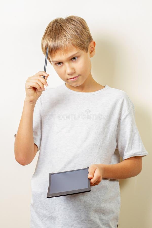 Jong geitje die wat denken om met grafische tablet en naaldpen te trekken stock afbeeldingen
