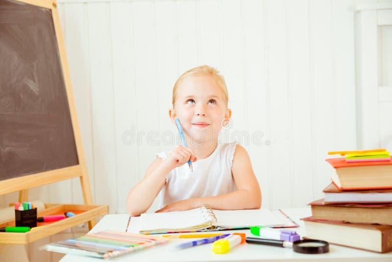 Jong geitje die wile doend haar thuiswerk denken royalty-vrije stock fotografie