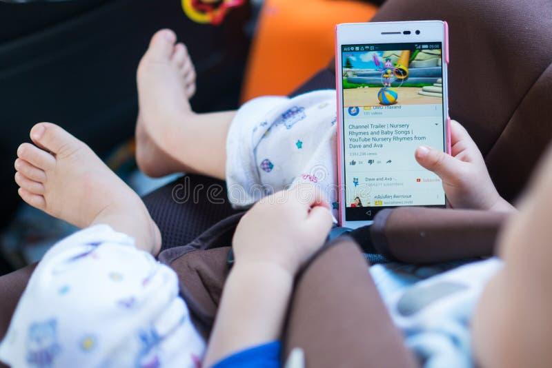 Jong geitje die youtube van smartphone letten op stock foto's