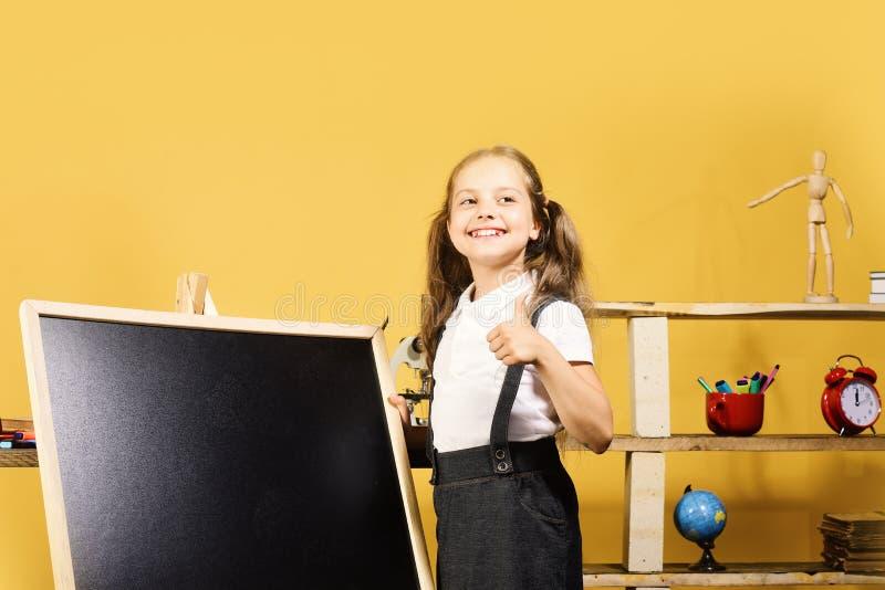 Jong geitje en schoollevering, gele achtergrond Schoolmeisje met vrolijk gezicht stock fotografie