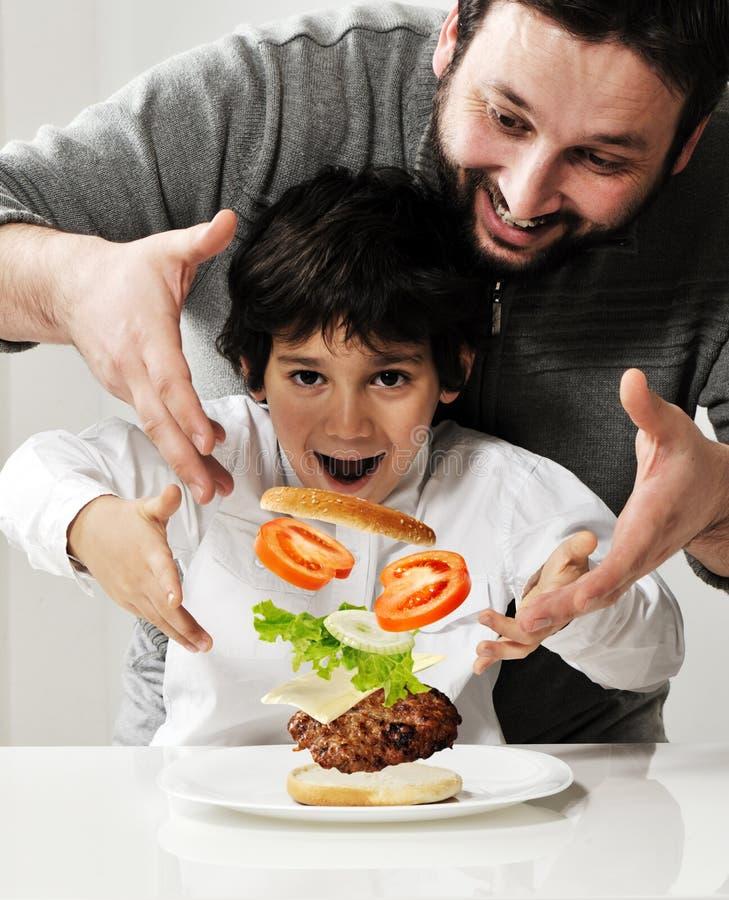 Jong geitje en vader die hamburger maken stock foto