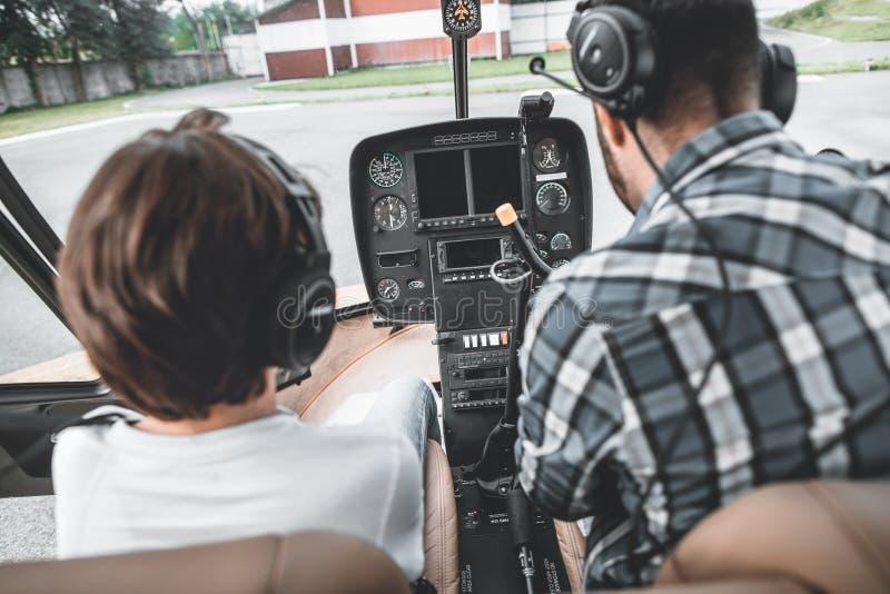 Jong geitje en volwassen zitting binnen eigentijdse helikopter royalty-vrije stock foto's