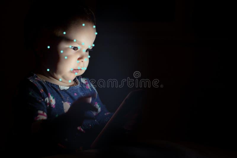 Jong geitje gebruikend de erkenning van gezichtsidentiteitskaart Jongen met een smartphonegadget Digitaal inheems kinderenconcept stock fotografie