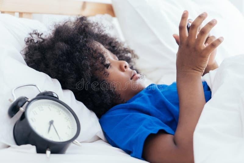 Jong geitje gebruikend smartphone met wekker die teveel tijd in de ochtend tellen royalty-vrije stock afbeeldingen