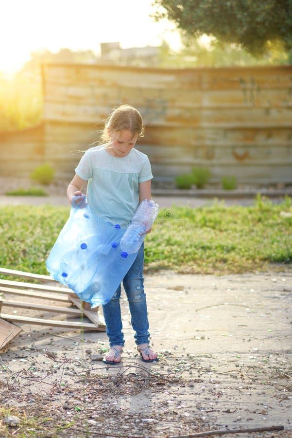 Jong geitje het schoonmaken in park Vrijwilligerskind met een vuilniszak die draagstoel schoonmaken, die plastic fles in het recy royalty-vrije stock fotografie