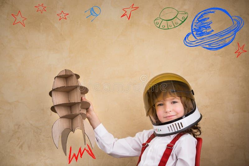 Jong geitje het spelen met kartonstuk speelgoed raket stock afbeeldingen