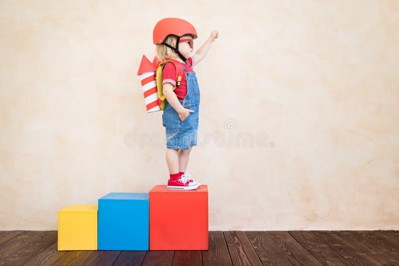 Jong geitje het spelen met stuk speelgoed raket thuis stock foto