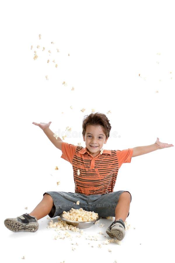 Jong geitje het spelen met zijn popcorn stock afbeelding