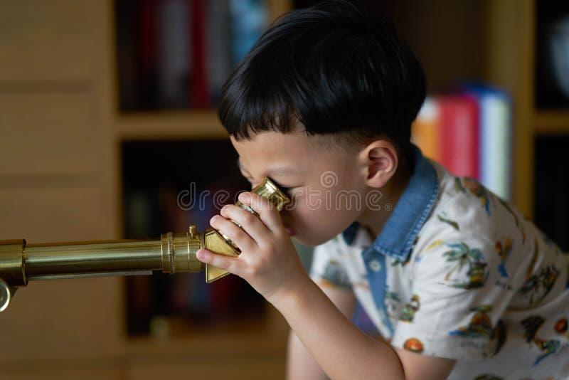 Jong geitje of jongensconcentratentelescoop binnen in nacht royalty-vrije stock foto