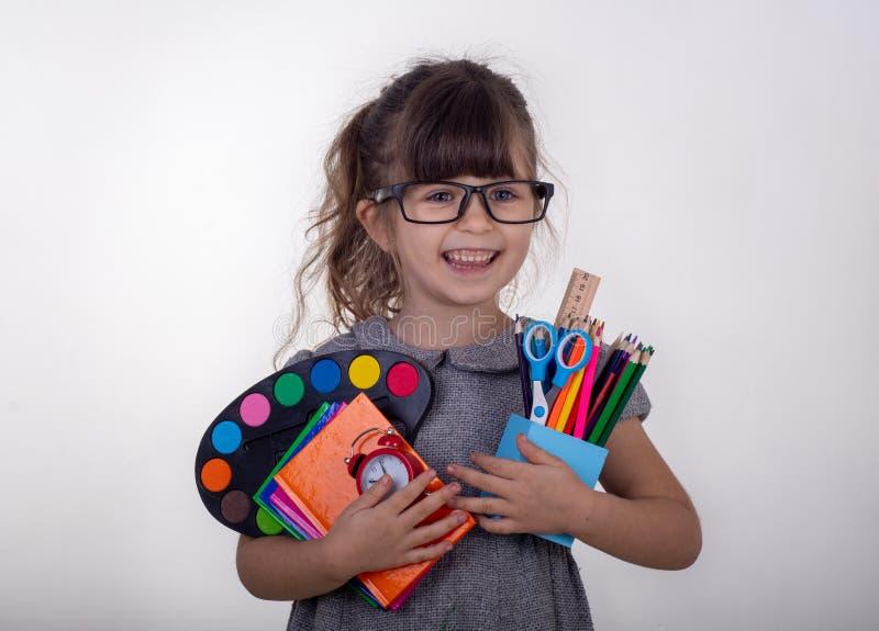 Jong geitje klaar voor school Leuk slim kind die in oogglazen schoollevering houden: pennen, notitieboekjes, schaar en appel stock fotografie