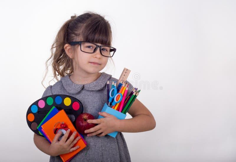 Jong geitje klaar voor school Leuk slim kind die in oogglazen schoollevering houden: pennen, notitieboekjes, schaar en appel stock foto's