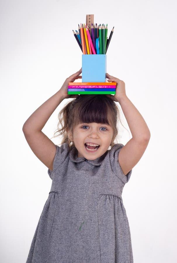 Jong geitje klaar voor school Leuke slimme de schoollevering van de kindholding: pennen, notitieboekjes, schaar op haar hoofd stock fotografie