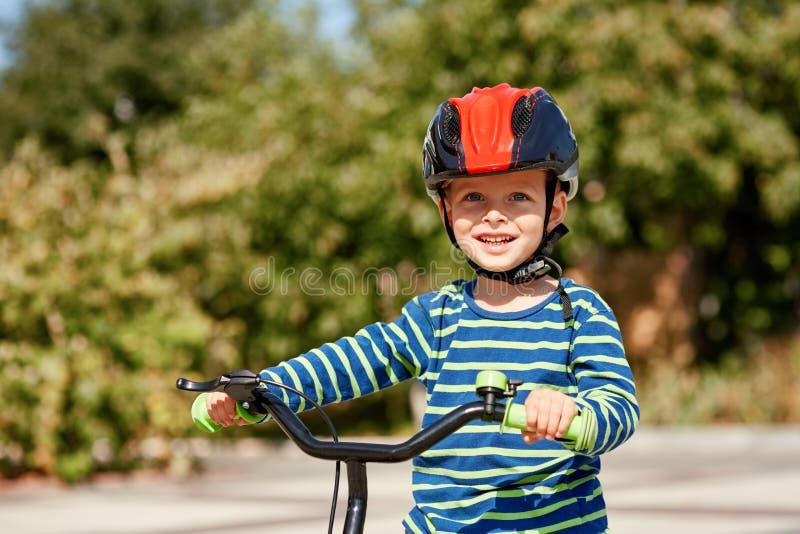 Jong geitje met fiets en helmglimlachen royalty-vrije stock foto